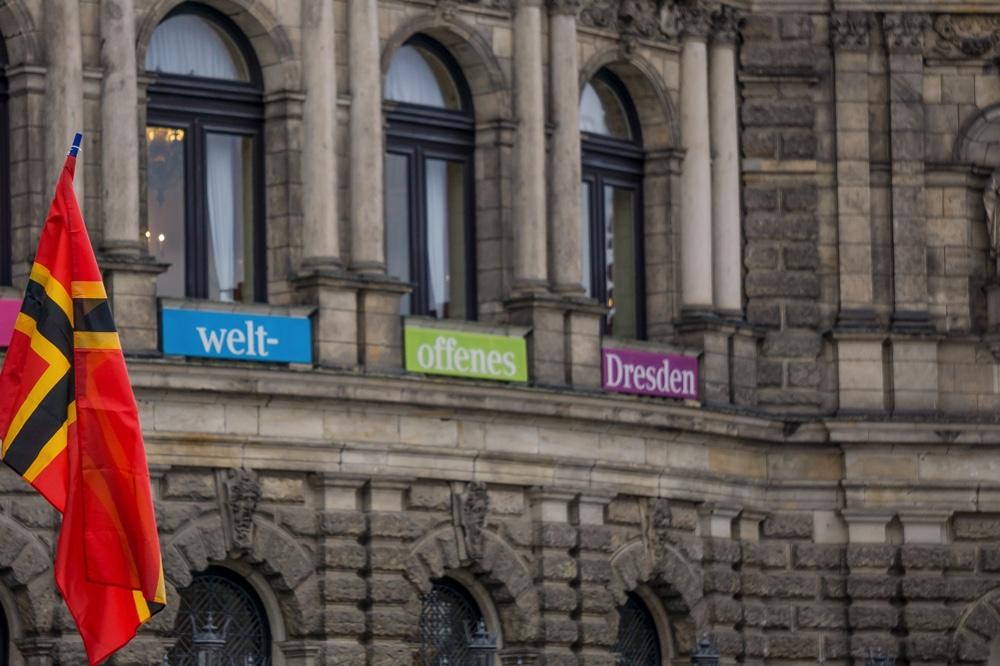 """3. PEGIDA Jahrestag in Dresden. Im Bild die Semperoper mit dem Transparent """"Für ein weltoffenes Dresden"""" und im Vordergrund die sogenannte Wirmler Flagge Copyright: Reiko Fitzke / rficture.com"""