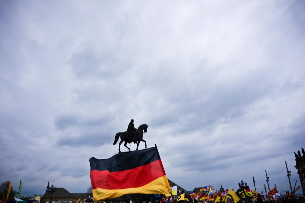 3. PEGIDA Jahrestag in Dresden. Im Bild die Statue vor der Semperoper und im Vordergrund die Deutschland Fahne Copyright: Reiko Fitzke / rficture.com