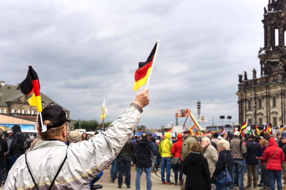 3. PEGIDA Jahrestag in Dresden. Im Bild ein Mann, der kleine Deutschland Fahnen schwenkt Copyright: Reiko Fitzke / rficture.com